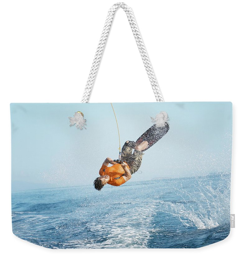 One Man Only Weekender Tote Bag featuring the photograph Man Performing Wakeboarding Stunt At Sea by Paul Bradbury