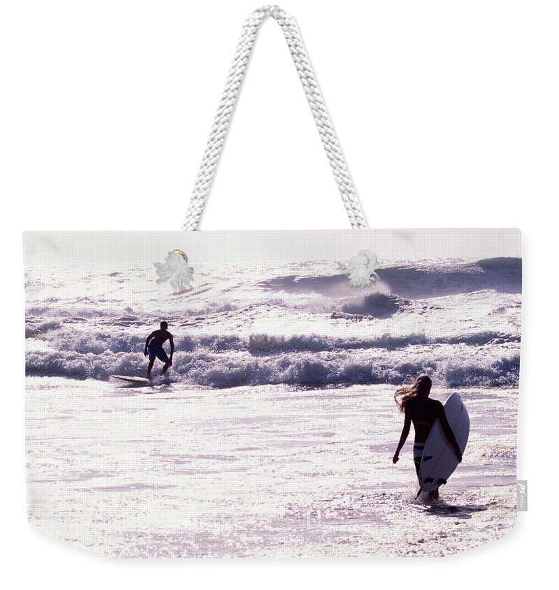 Wind Weekender Tote Bag featuring the photograph Man Surfing On Sea, Woman Walking With by Johner Images