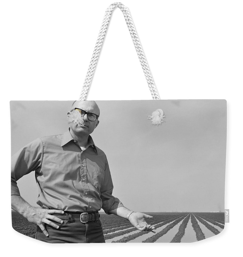 Mature Adult Weekender Tote Bag featuring the photograph Mature Man Gesturing At Ploughed Field by Tom Kelley Archive