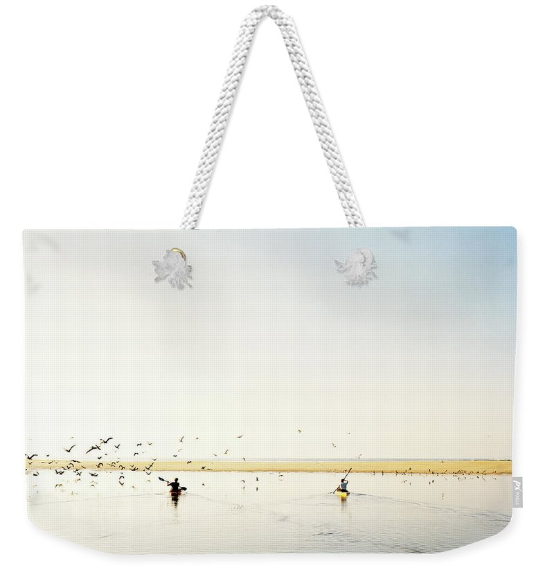 People Weekender Tote Bag featuring the photograph Men Paddling Kayaks To The Beach by Julien Capmeil
