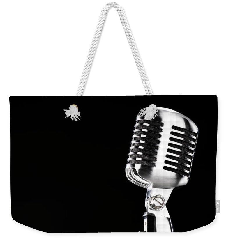 Music Weekender Tote Bag featuring the photograph Microphone Against Black Background by Peter Dazeley