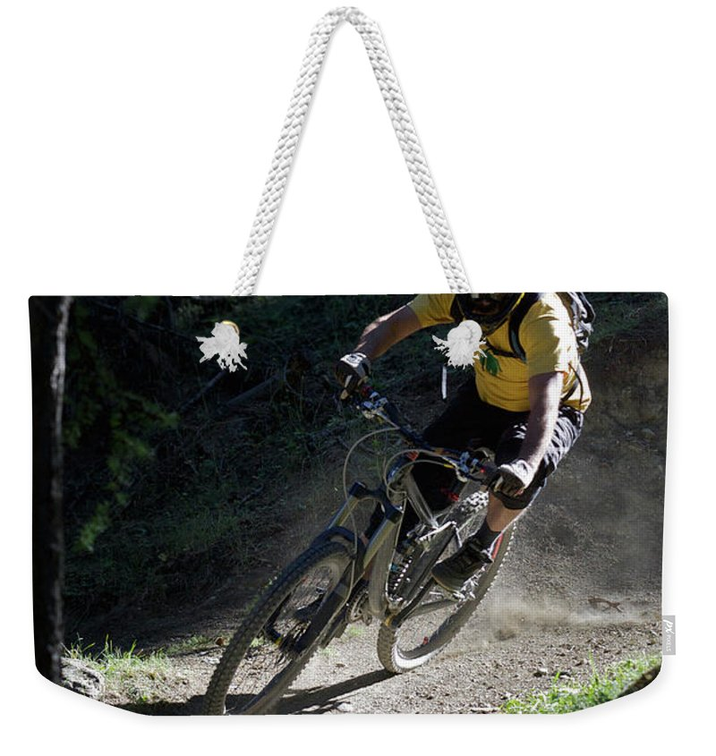 Sports Helmet Weekender Tote Bag featuring the photograph Mountain Biker On Dirt Path by Michael Truelove