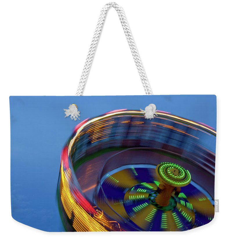 Carousel Weekender Tote Bag featuring the photograph Multicolored Spinning Carnival Ride by By Ken Ilio
