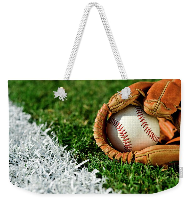Grass Weekender Tote Bag featuring the photograph New Baseball In Glove Along Foul Line by Cmannphoto