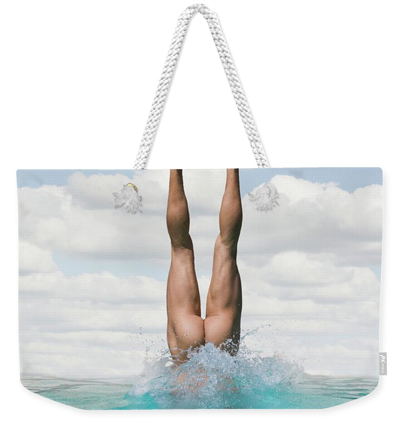 Diving Into Water Weekender Tote Bag featuring the photograph Nude Man Diving by Ed Freeman