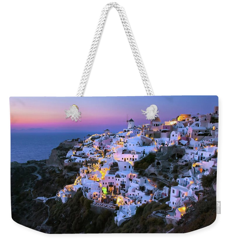Greek Culture Weekender Tote Bag featuring the photograph Oia Lights At Sunset by Greg Gibb Photography