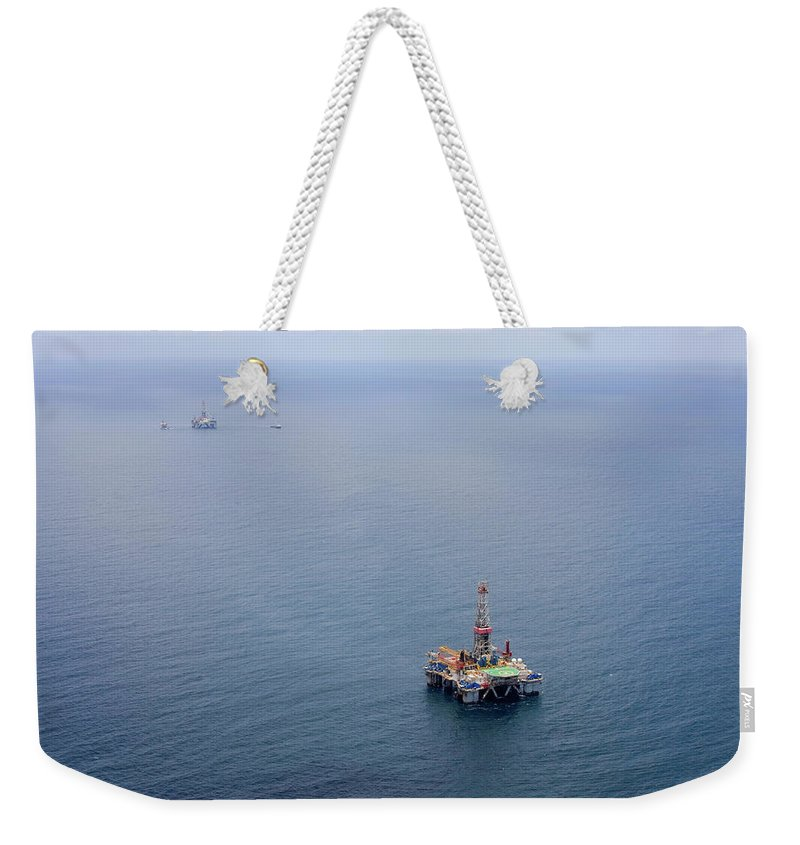 Convoy Weekender Tote Bag featuring the photograph Oil Rigs by Heliry