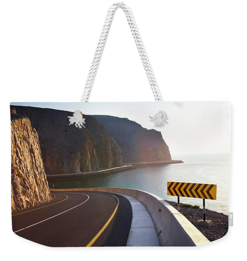 Curve Weekender Tote Bag featuring the photograph Oman, Khasab, Road Round Mountain By by Christian Adams