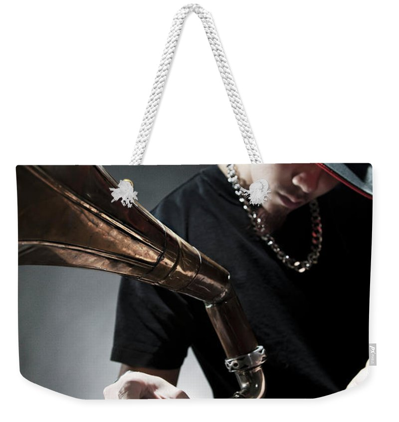 Youth Culture Weekender Tote Bag featuring the photograph Oriental Dj Using Old Gramophone To Mix by Justin Lambert