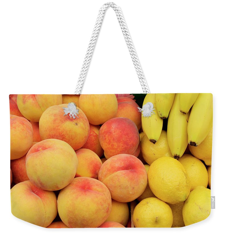 Retail Weekender Tote Bag featuring the photograph Peaches, Lemons And Bananas At Farmers by Travelif