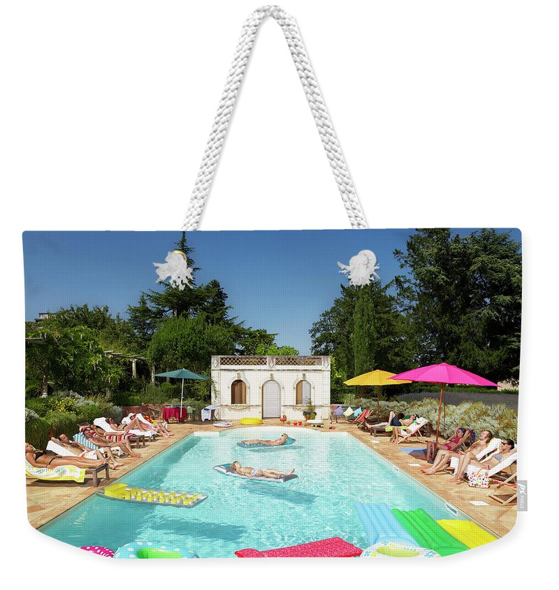 Young Men Weekender Tote Bag featuring the photograph People Enjoying Summer Around The Pool by Ghislain & Marie David De Lossy