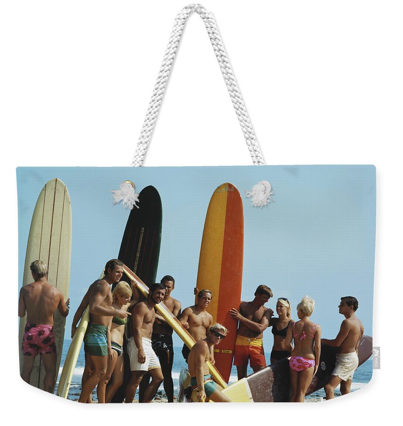 People Weekender Tote Bag featuring the photograph People On Beach With Surf Board by Tom Kelley Archive