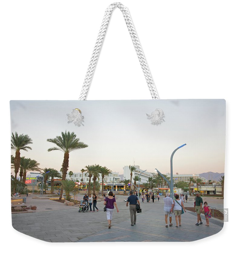 Child Weekender Tote Bag featuring the photograph People Walking On Stone Plaza Near Palm by Barry Winiker