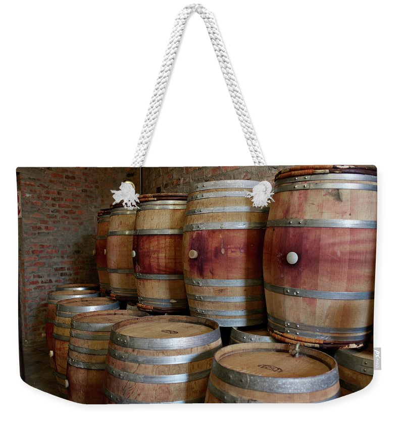 Stellenbosch Weekender Tote Bag featuring the photograph Pile Of Wooden Barrels At Winery by Klaus Vedfelt