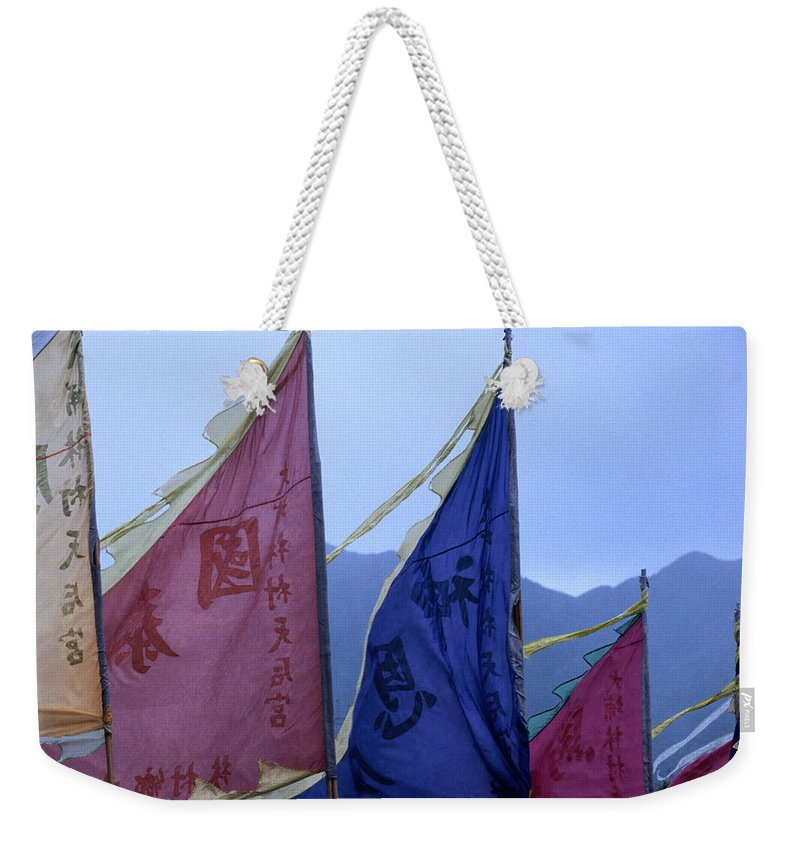 Chinese Culture Weekender Tote Bag featuring the photograph Prayer Flags To The Sea Goddess Blow In by Lonely Planet