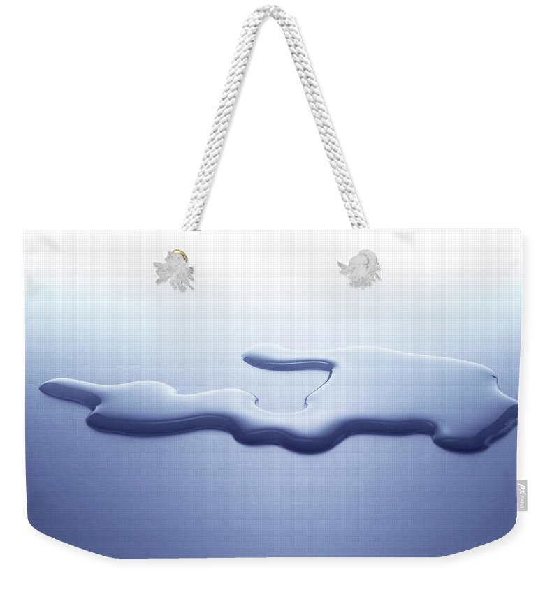 Purity Weekender Tote Bag featuring the photograph Puddle Of Water On White Surface by Nicholas Eveleigh