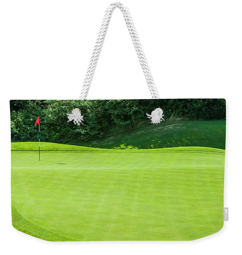 The End Weekender Tote Bag featuring the photograph Putting Green And Flag At A Golf Course by Stuart Dee