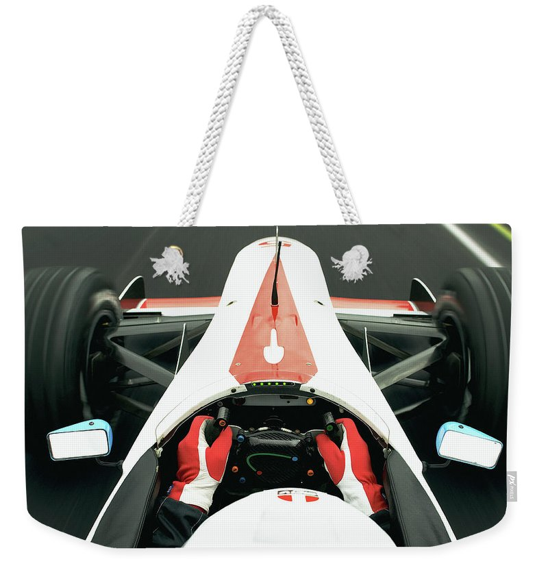 Aerodynamic Weekender Tote Bag featuring the photograph Racing Driver Approaching Finishing by Alan Thornton