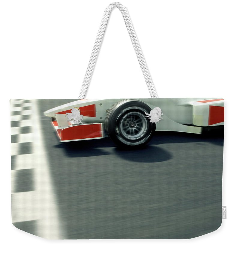Aerodynamic Weekender Tote Bag featuring the photograph Racing Driver Crossing Finishing Line by Alan Thornton