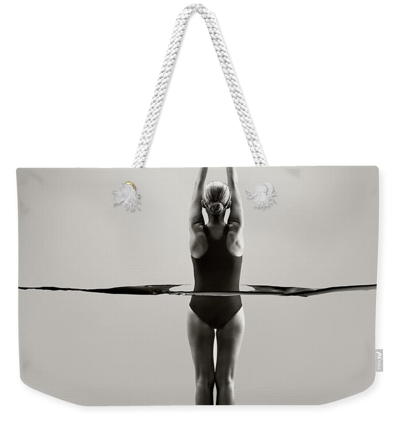 Diving Into Water Weekender Tote Bag featuring the photograph Rear View Of Female Swimmer by Jonathan Knowles