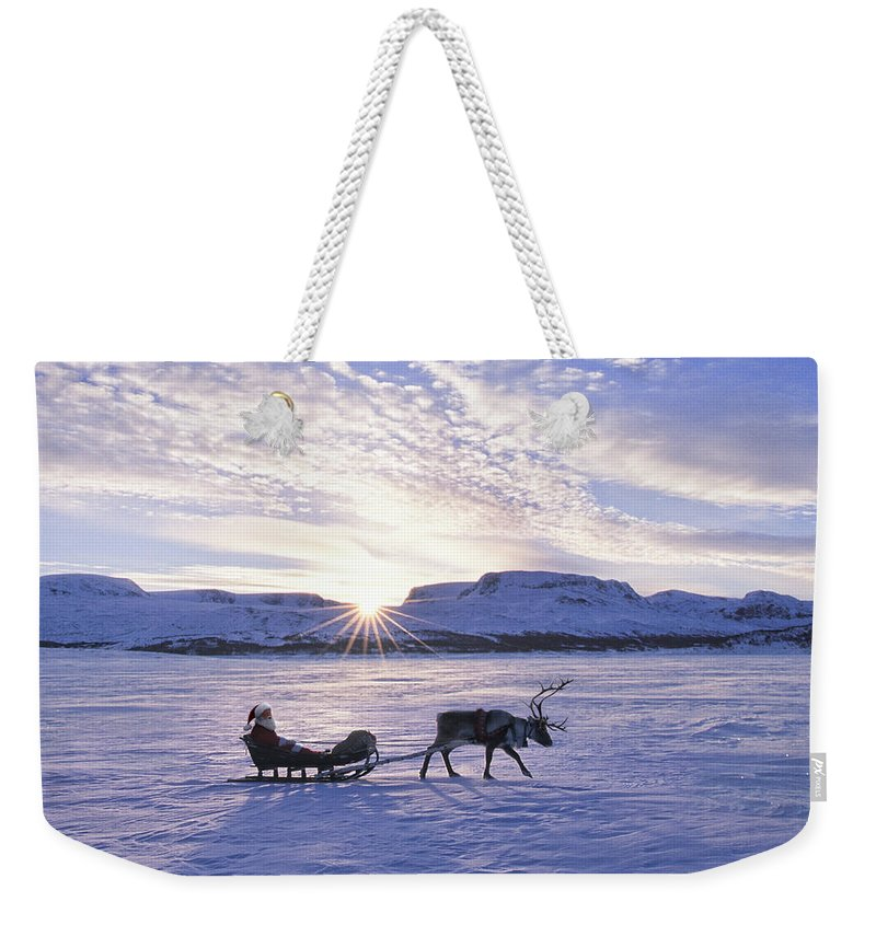 One Man Only Weekender Tote Bag featuring the photograph Reindeer Pulling Santa On Sled Over by Per Breiehagen