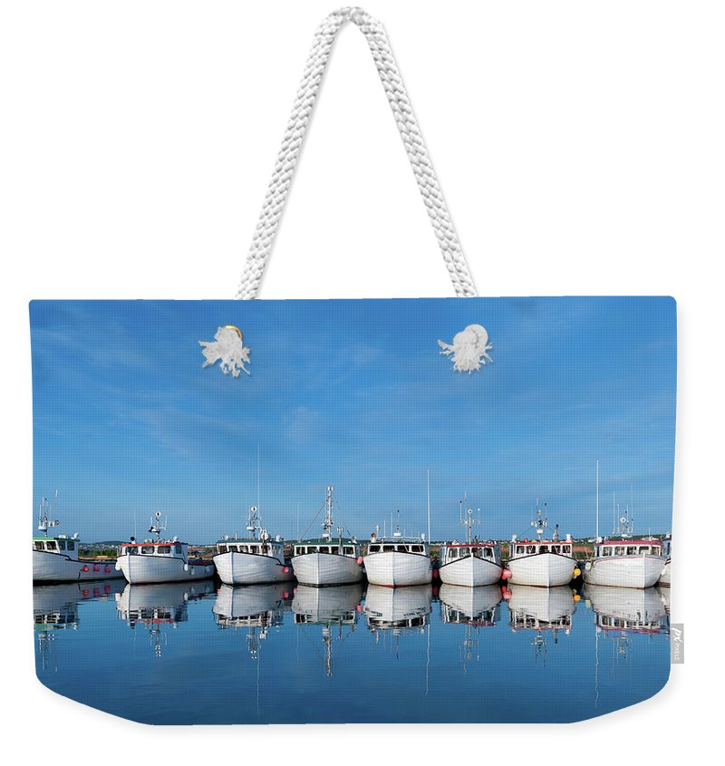 Iles De La Madeleine Weekender Tote Bag featuring the photograph Row Of Boats With Reflection by Pndtphoto