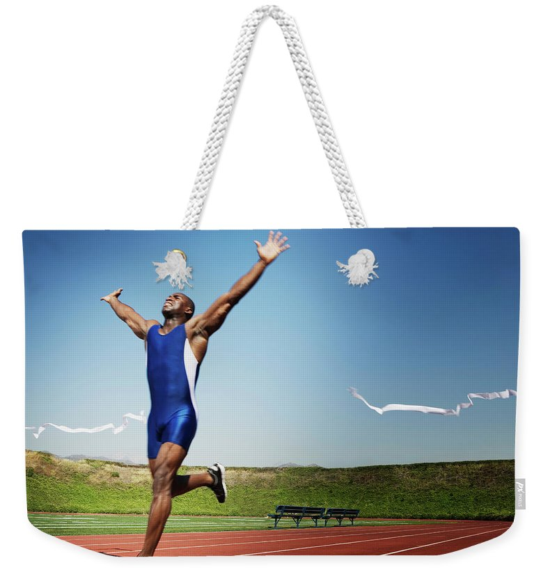 Human Arm Weekender Tote Bag featuring the photograph Runner Crossing Finish Line by Jupiterimages