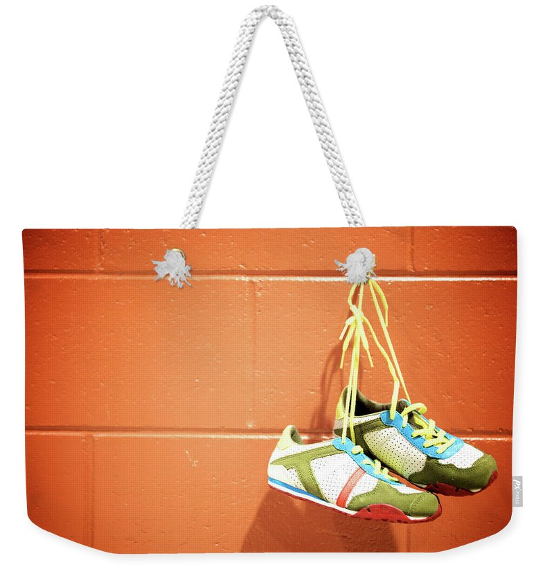 Hanging Weekender Tote Bag featuring the photograph Runnig Shoes Hanging On A Hook by Pascalgenest
