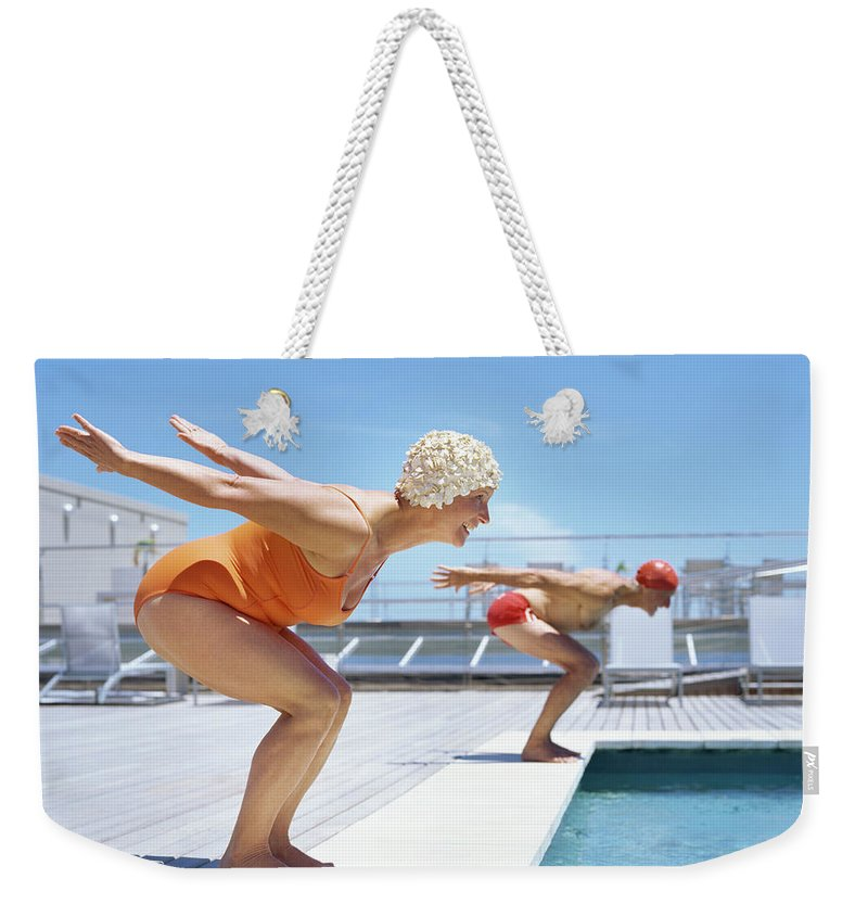 Diving Into Water Weekender Tote Bag featuring the photograph Senior Couple Ready To Dive In To by Stockbyte