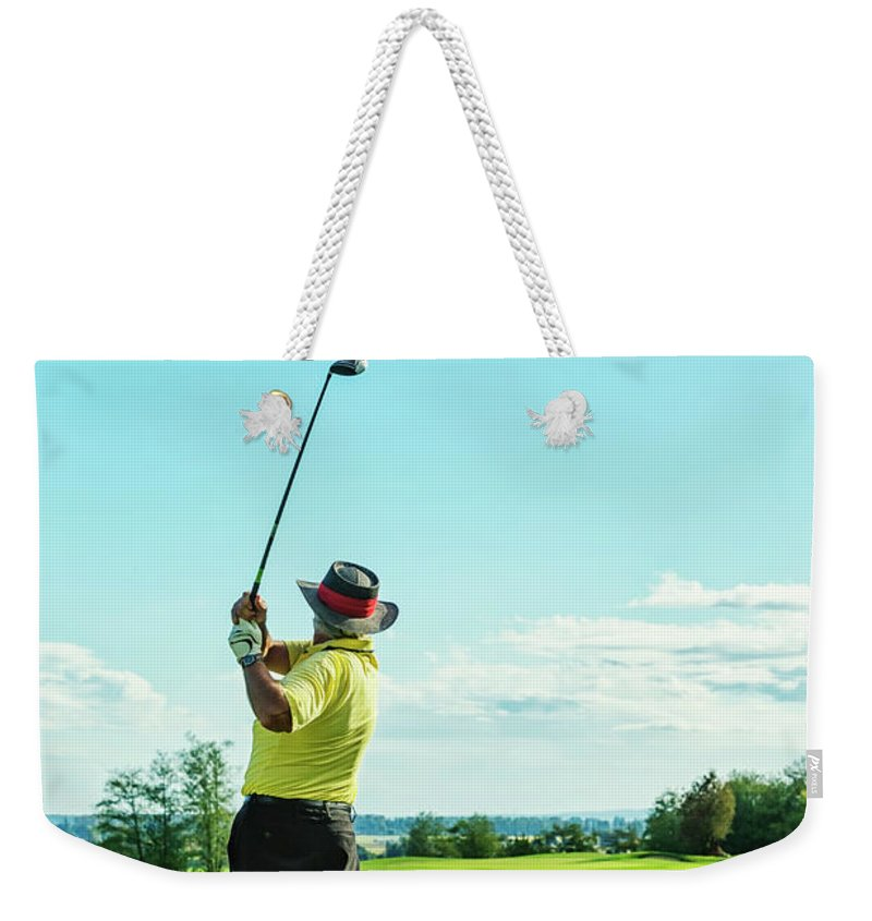Expertise Weekender Tote Bag featuring the photograph Senior Golfer On Golf Course Teeing Off by Jhorrocks