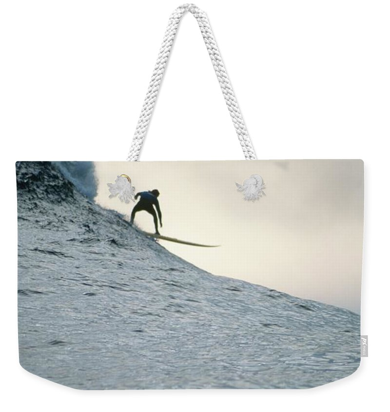 Scenics Weekender Tote Bag featuring the photograph Silhouette Of A Surfer Riding A Wave by Dominic Barnardt