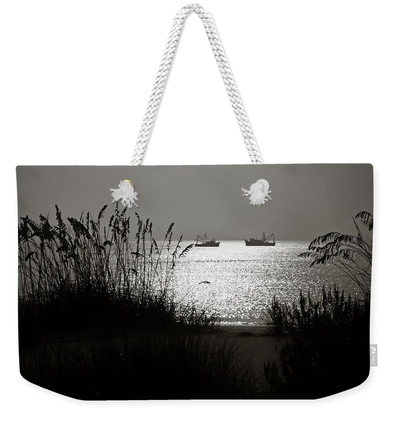 Tranquility Weekender Tote Bag featuring the photograph Silhouettes Of Sea Oats And Shrimp Boats by Joseph Shields