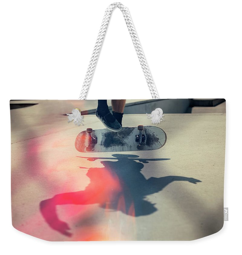 Cool Attitude Weekender Tote Bag featuring the photograph Skateboarder Doing An Ollie by Devon Strong