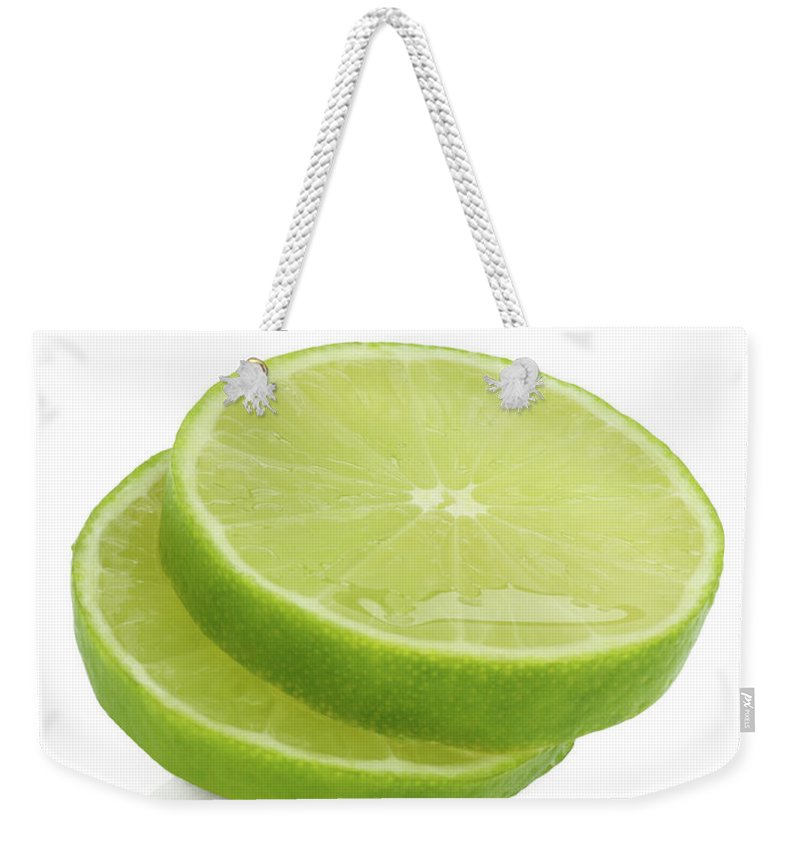White Background Weekender Tote Bag featuring the photograph Slices Of Fresh, Juicy, Freshly Cut Lime by Rosemary Calvert