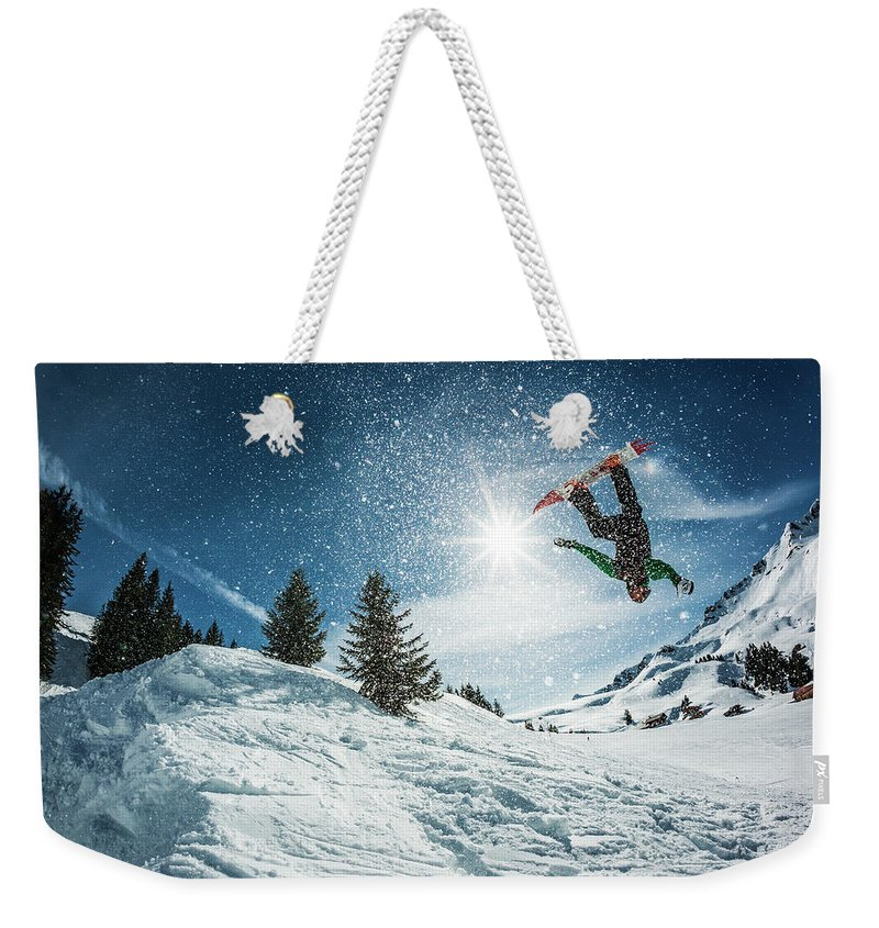 People Weekender Tote Bag featuring the photograph Snowboarder Doing A Backflip With Snow by © Francois Marclay