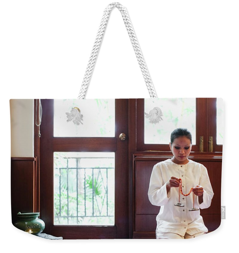 Spa Weekender Tote Bag featuring the photograph Spa Therapist Prepares Massage Room by Matthew Wakem