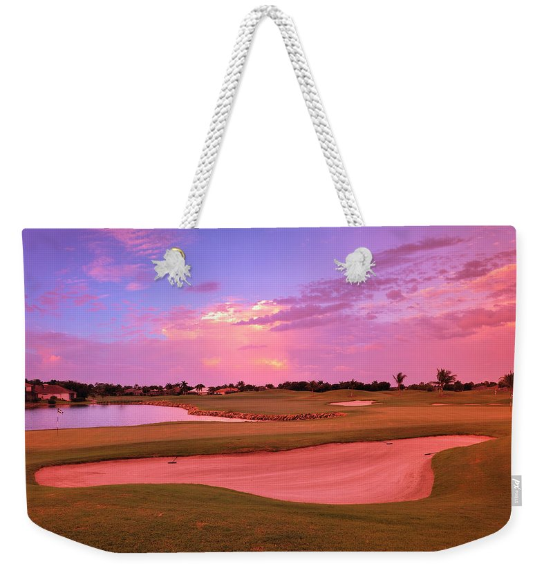 Sand Trap Weekender Tote Bag featuring the photograph Sunrise View Of A Resort On A Golf by Rhz