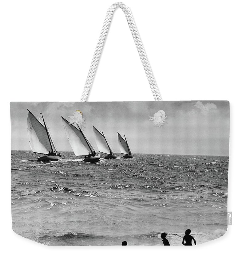 Following Weekender Tote Bag featuring the photograph Three Boys Running Along Beach by Stockbyte