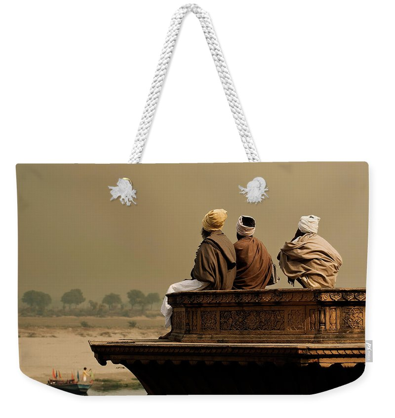 Water's Edge Weekender Tote Bag featuring the photograph Three Sadhus Meditating By The Yamuna by Globalstock