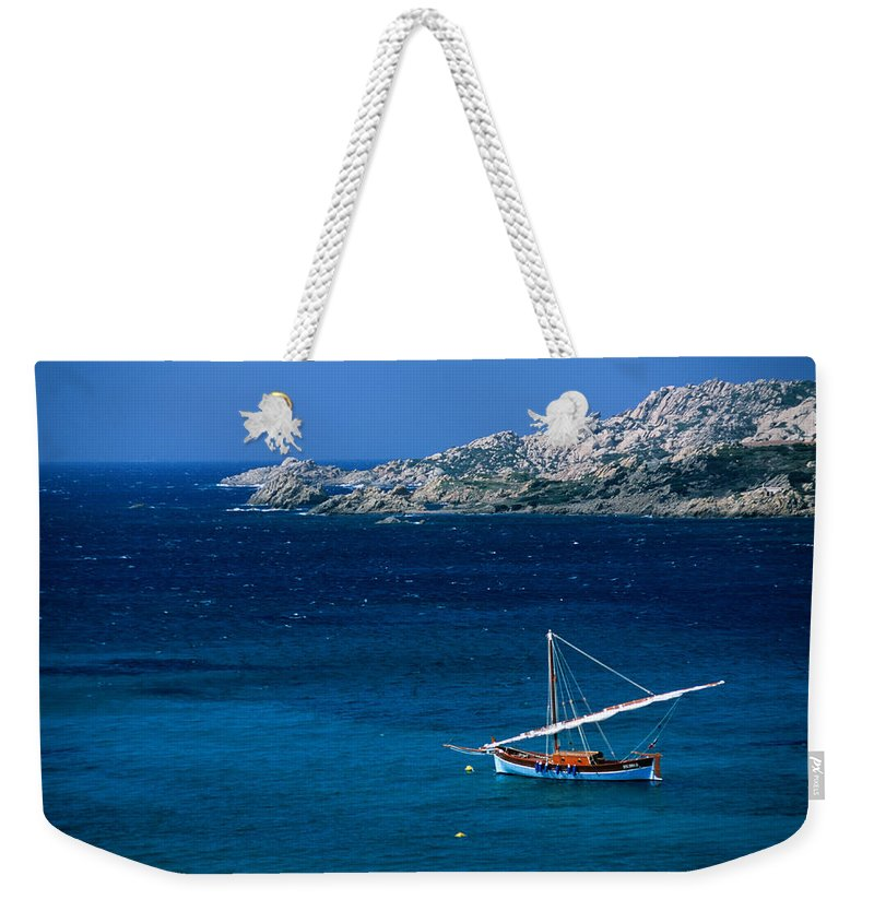 Sailboat Weekender Tote Bag featuring the photograph Traditional Sailboat On Rocky Coast Of by Dallas Stribley