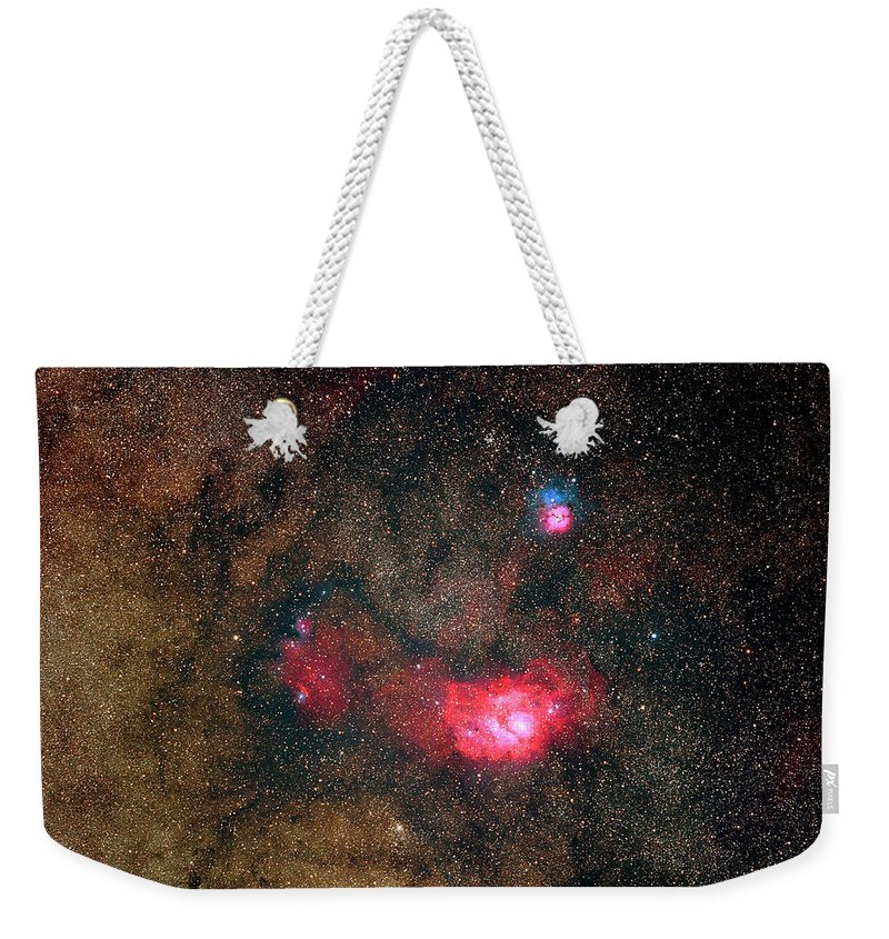 Sky Weekender Tote Bag featuring the photograph Trifid Nebulae And Lagoon Nebula by Imagenavi