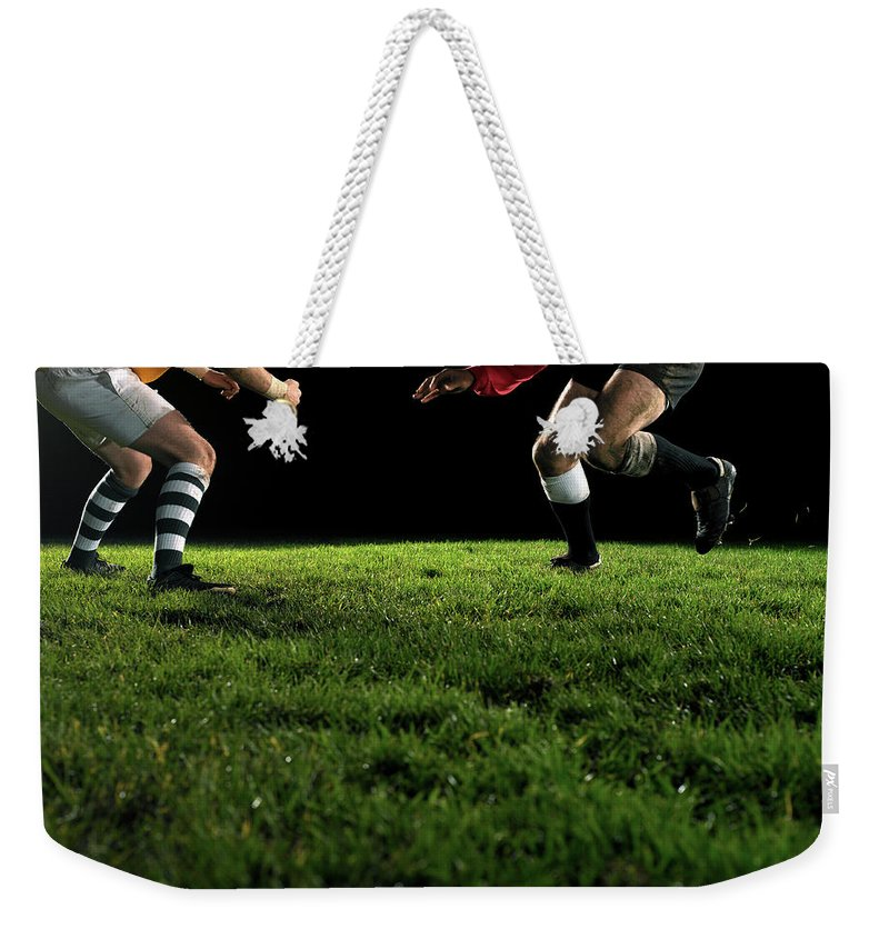 Grass Weekender Tote Bag featuring the photograph Two Opposing Rugby Players, One Holding by Thomas Barwick
