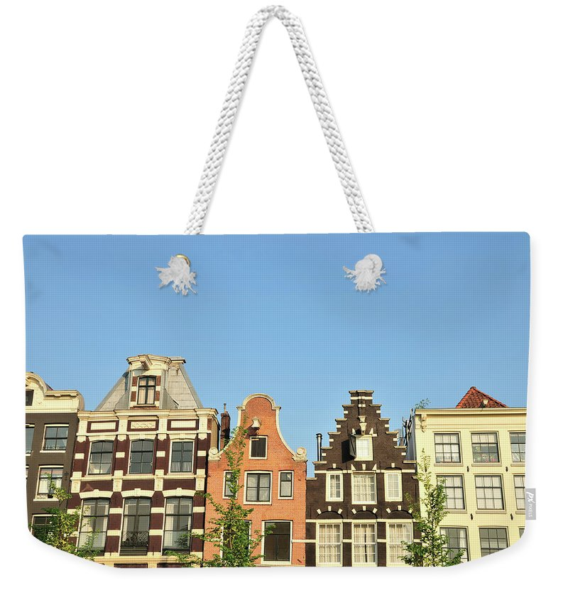 In A Row Weekender Tote Bag featuring the photograph Typical Canal Houses, Amsterdam, The by Gorazdbertalanic