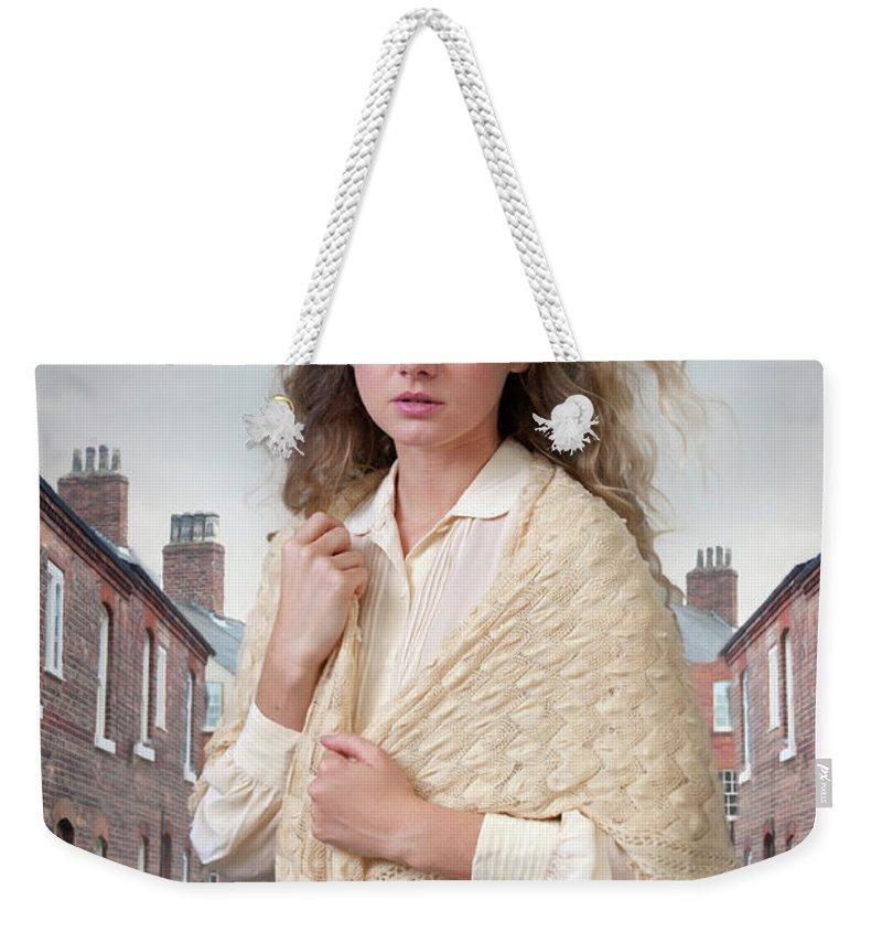Victorian Weekender Tote Bag featuring the photograph Victorian Woman On A Cobbled Terraced Street by Lee Avison