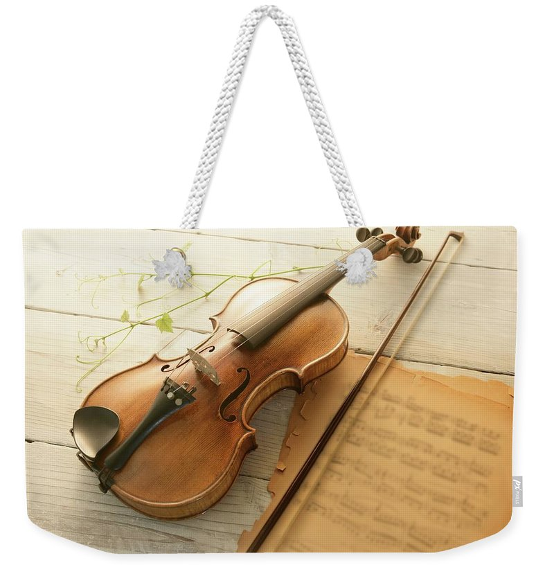 Sheet Music Weekender Tote Bag featuring the photograph Violin And Music Sheet by Image Work/amanaimagesrf
