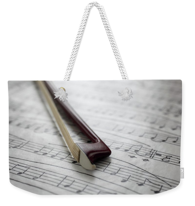 Sheet Music Weekender Tote Bag featuring the photograph Violin Bow On Music Sheet by Daniel Allan
