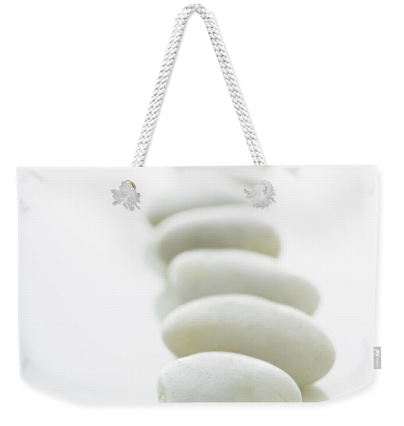 White Background Weekender Tote Bag featuring the photograph White Stones Lined Up On A White by Rick Lew