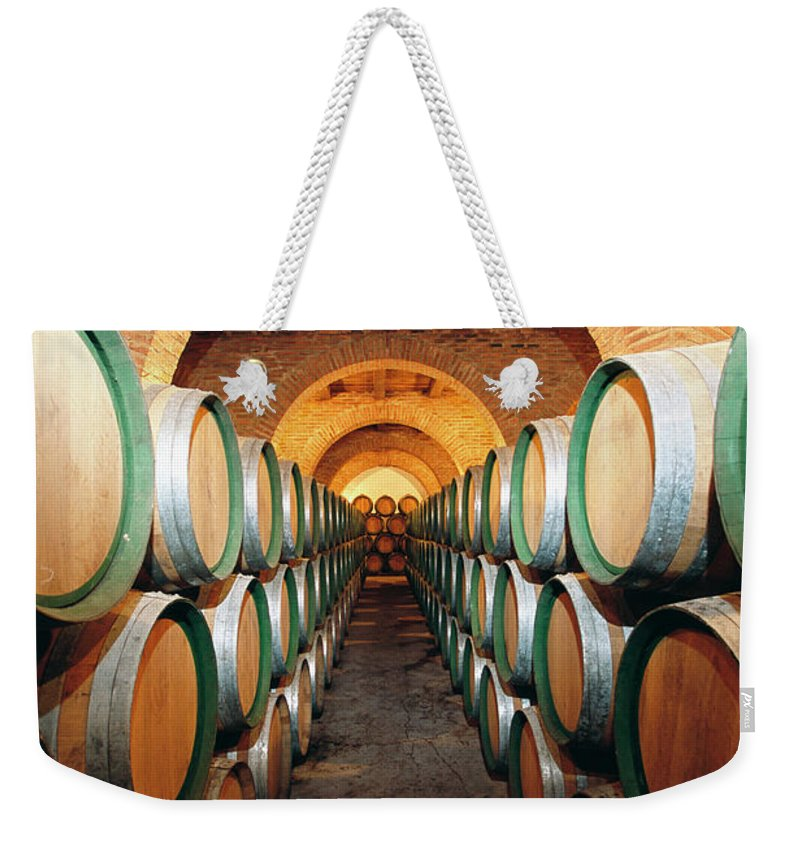 Working Weekender Tote Bag featuring the photograph Wine Barrels In Cellar, Spain by Johner Images