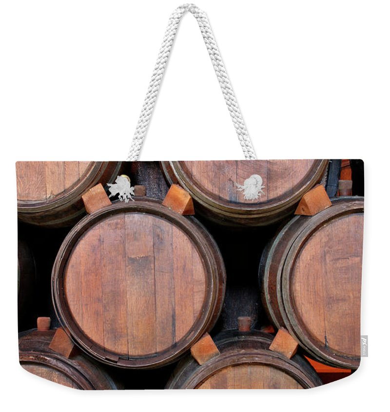 Fermenting Weekender Tote Bag featuring the photograph Wine Barrels Stacked Inside Winery by Yinyang
