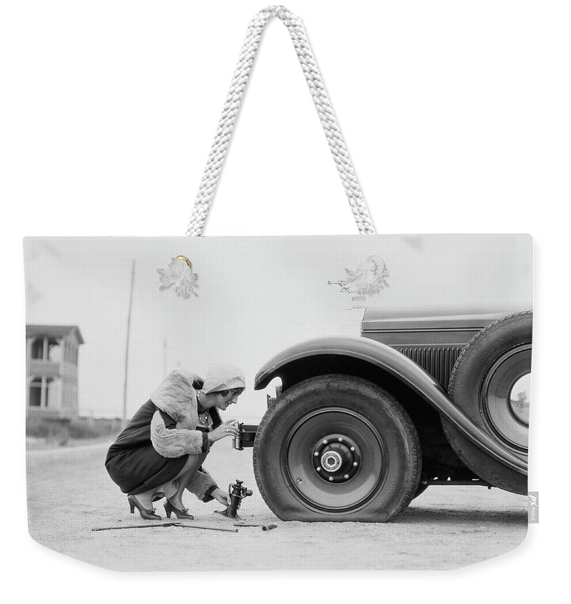People Weekender Tote Bag featuring the photograph Woman Changing Flat Tire On Car by H. Armstrong Roberts